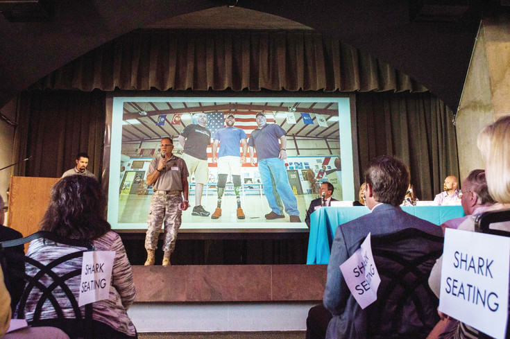 A representative from the Warrior Bonfire Program speaks to potential donors about providing Purple Heart recipients with trips around the country at South Metro Denver Chamber's event, The Tank, at the Denver Botanic Gardens.