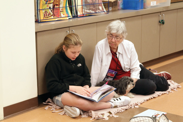 Charley Barker, 10, reads to therapy dog Molly and her owner Sylvia Colling during the March 18 Paws to Read event at the Englewood Public Library.