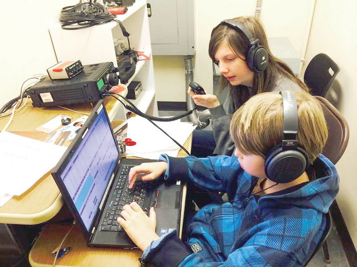 Anna Veal, back, mentors a fellow STEM School and Academy student on how to use an amateur radio, also called a ham radio. The technology uses radio frequencies to communicate with other radio users.