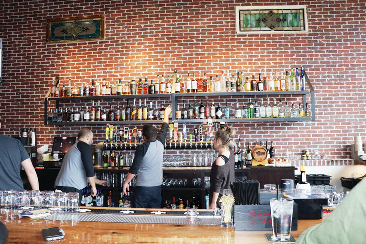 An employee replaces a bottle on the bottom shelf on the rear wall of Whiskey Biscuit Restaurant and Tavern. The two shelves carry a wide selection of spirits plus there are 28 draft beer taps to choose from.