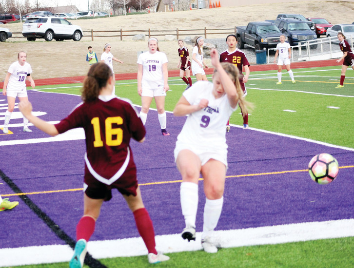 Lutheran's  Ally Tripp (9) protects herself as Ponderosa's Myah Thornhill (16) kicks the ball away during the non-league soccer game March 27 at Lutheran. The Mustangs won. 10-0.