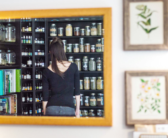 Dani Otteson, a community Herbalist who recently opened her business, Milkweed Herbarium, stands in front of her shelf of herbs and teas. Otteson teaches classes about using herbs for wellness and medicine.