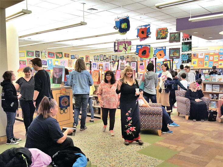 Teachers, school board members and officials joined parents and their children at the April 5 reception. Wires had to be strung from the ceiling in order to display all the hundreds of artworks selected for the annual show.