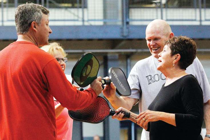 Pickleball players tap paddles at the end of a match, a universally honored custom withinthe game. Among those pictured are Ann Yannacone, left rear, Dick Barton, right rear, and Sharon Warrender, right. The player on the left was playing hooky from work and chose not to give his name.