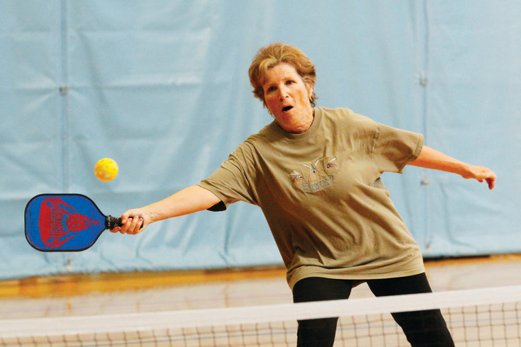 Aurora's Pat Kraft, a former tennis player, reaches to return a shot in a pickleball match on April 3. Many tennis players gravitate to the sport for the fast action and exercise without the joint strain caused by running on tennis' larger, harder courts