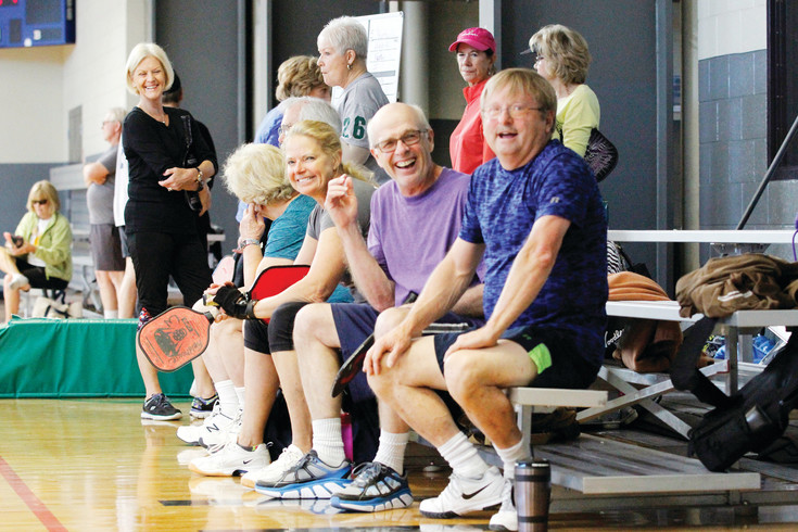 Pickleballers at the Parker Fieldhouse enjoy a break in the action as they wait for an open court. Sports Supervisor Bob Bullock says he often had to fill in when the center first offered the games, but now an average of 45 players show up daily.