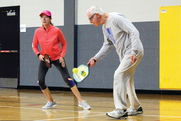 "Christel Gibbons of Aurora and Kirby Fisher of Parker hold court during a weekday drop-in pickleball game at the Parker Fieldhouse. The sport's inventors reportedly named the game after one of their dogs, ""Pickles,"" that loved to take balls and hide them."
