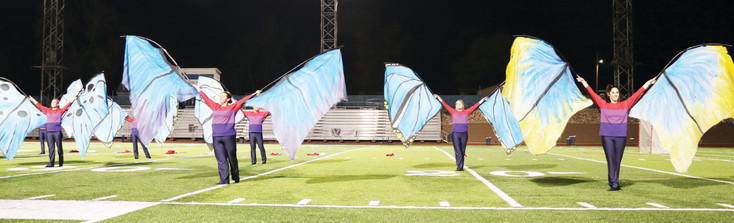 The Blue Knights-Bahrain color guard maneuvered life-sized butterfly wings at a performance at Englewood High School on April 11. The 100-person ensemble left for Bahrain, an island in the Persian Gulf, the following day to perform at the Grand Prix, a Formula One Championship car race.