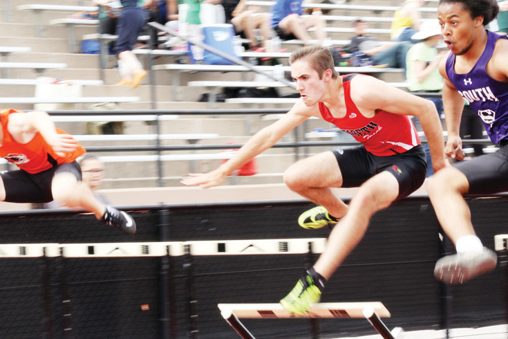 Elizabeth's Ben Humphrey pushes to stay ahead of the Denver South athlete during the 110-meter high hurdle heat race at the April 7 Thomas Jefferson Twilight Invitational Track Meet. Humphrey finished 20 in the overall event standing with a finals time of 18.96 seconds. The Cardinal boys finished 19th among the 26 schools in the team standings.