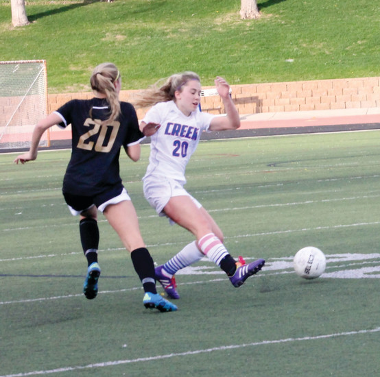 Defender Natalie Evans of Cherry Creek (20) kicks the ball away from Arapahoe's Camryn MacMillan (20) during the April 13 Centennial League soccer match at the Stutler Bowl. Creek scored four times in the second half to post a 4-0 victory over rival Arapahoe.