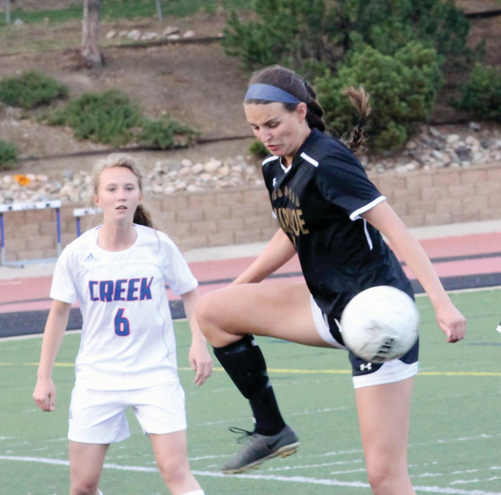 Arapahoe's Maddie Hahn tries to control the ball as Cherry Creek's Jackie Lasseter watches during the April 13 Centennial League soccer game at the Stutler Bowl. Creek scored four goals in the second half on a windy evening to earn a 4-0 victory over the Warriors.