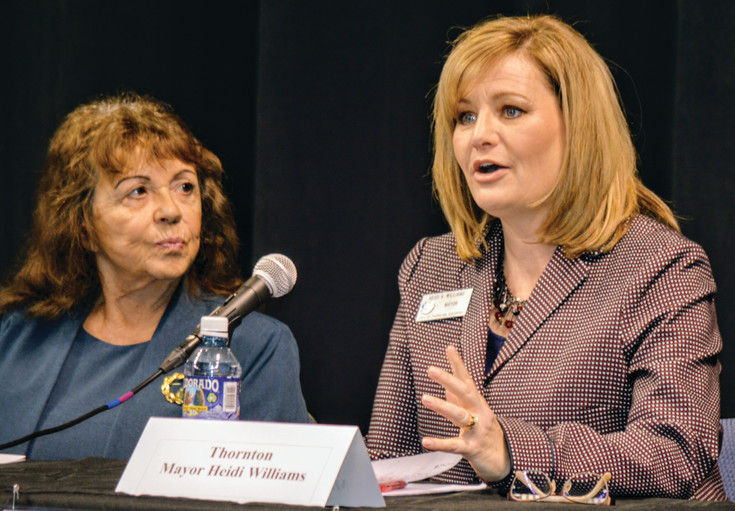 Northglenn Mayor Joyce Downing listens as Thornton Mayor Heidi Williams makes a point April 13 at the Metro North Chamber of Commerce's State of the Region conference at 1st Bank Center in Broomfield.