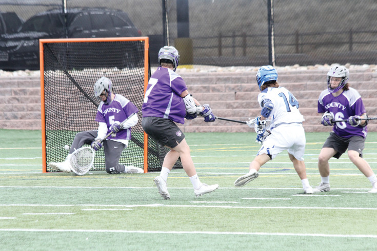 Douglas County goalie Denton Skelton (5) reached down to scoop up a shot for Highlands Ranch by Jake Lynn (14) during the April 11 league boys lacrosse game. Skelton made 16 saves in the game but Highlands Ranch pushed the attack late and won the game, 16-9.