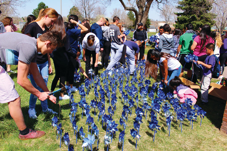 Volunteers have placed blue pinwheels around the area in observance of National Child Abuse Prevention & Awareness Month. Locally, the pinwheels are placed in honor of Ralston House.