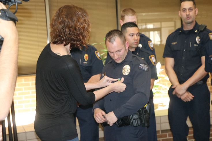 Diane Eckert, who lost her brother Cody Crosby in a car accident in 2013, pins a Donate Life pin on Arvada Police Officer Derek Berns. Berns witnessed the accident that killed Crosby, and was the first to respond to the situation. Crosby was an organ and tissue donor, and his organs saved several lives.