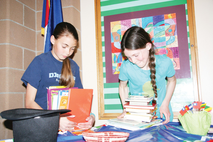 Fifth-graders Elise Henderson and Kyra Jordan stack the books already collected for Mitchell Elementary School's Global Library. Henderson started the library as a way to welcome students who speak a language other than English to the school community.