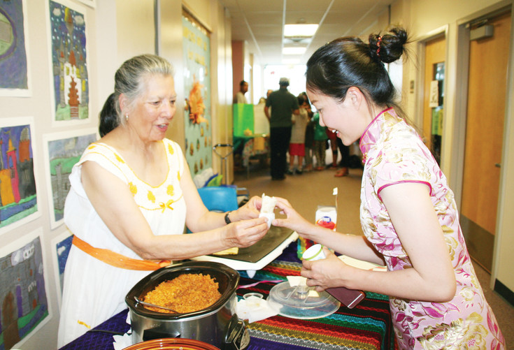Katie Valverde, left, serves Fang Ding of China a warm tortilla filled with rice, beans and cactus, as is eaten in Mexico. Valverde is a grandmother of a student at Mitchell, and Ding has a son who attends Mitchell. Both were participating in the school's Multicultural Night on April 12.