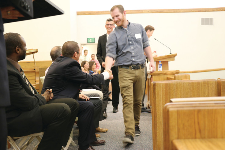 Kellen Healy, a ThunderRidge High School teacher recognized for his efforts with students, shakes the hand of principal Chris Tabeling at the annual Teacher Appreciation Banquet at the Church of Jesus Christ of Latter-Day Saints on April 12.