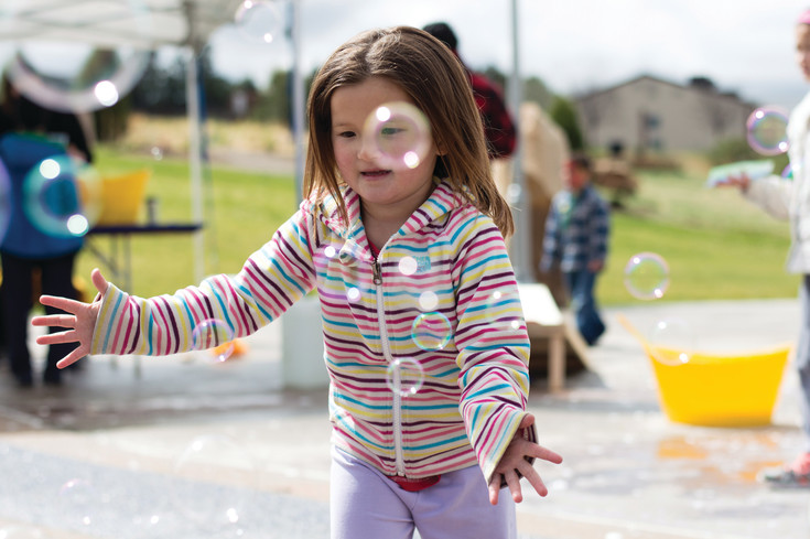 Elizabeth Phan pops the bubbles in the kid's play area durring Centennial's Earth Day celebration.