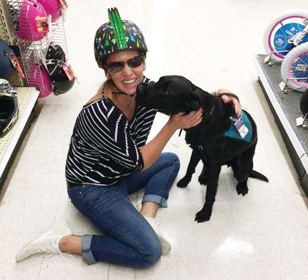Elise Hunt and her assistance dog Cowboy share a hug during a training session with paws4vets staff at a Toys 'R' Us store in North Carolina. The trainings are held in public to trigger PTSD symptoms in veterans and train dogs how to respond to those symptoms as well as stimuli like loud noises.