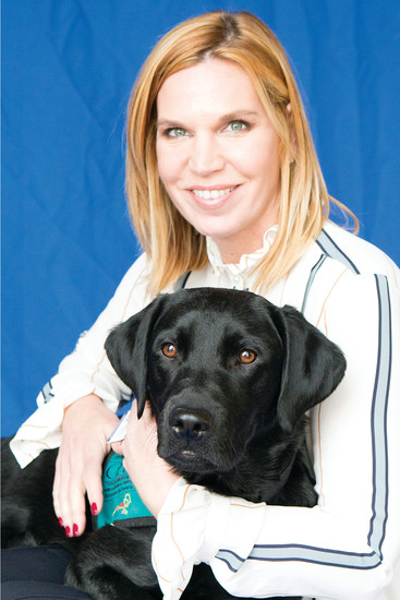 Unted States Army veteran Elise Hunt poses with her companion canine COWBOY, a gift from the paws4vets nonprofit. Hunt recently gave a presentation to students at North Star Academy in Parker about how to approach assistance dogs and what the animals do to help veterans with PTSD.