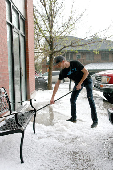 Jordyn Drayton, service manager at the Golden Bike Shop, shovels hail outside of the service side of the shop after a late afternoon hailstorm on May 8. The hail only lasted about 20 minutes, but coated the city. Drayton had to remove the hail from the shop's side doorway because as it melted, it instantly started to seep into the shop to an area near where the IT equipment is stored, he said.