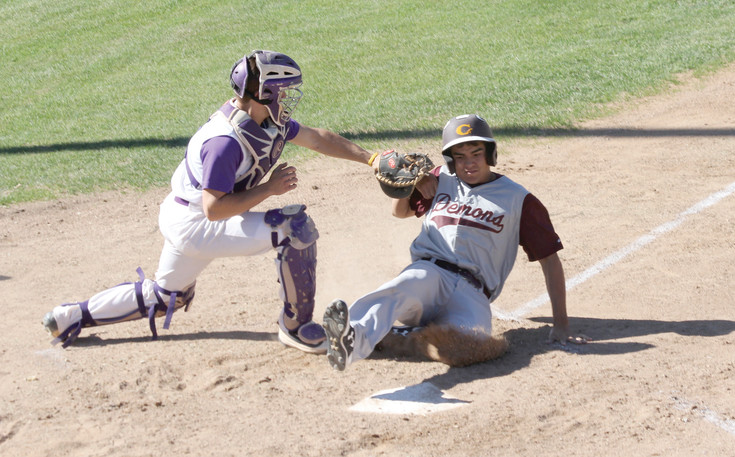 Ben McLaughlin slides safely into home plate scoring a run for Golden despite efforts by Littleton catcher Jared Dreiling during the May 5 league baseball playoff game. The Demons would go on to score four runs in the top of the seventh inning and turned back a Lions rally in the home half of the inning to win, 11-10.
