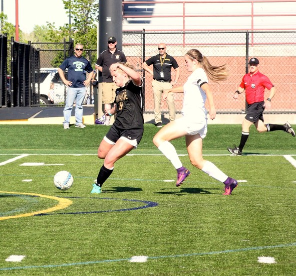 Arapahoe senior center back Sydney Maxson (9)  clears the ball away from ThunderRidge's Shae Holmes during the second round Class 5A soccer playoff game on May 12 at Shea Stadium. Maxson scored on a free kick in the 57th minute  to lift the Warriors to a 1-0 victory.