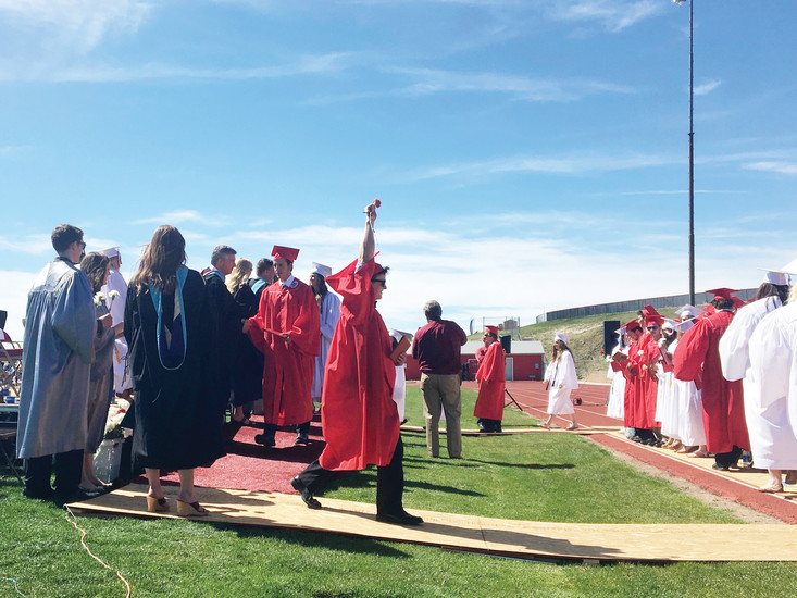 A newly minted graduate throws his hand in the air as seniors line up to receive their diplomas and shake hands with Principal McClendon and Superintendent Bissonette.