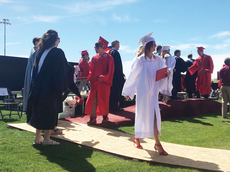 A stylish graduate wears red heels to complement her white gown and and the Elizabeth High School colors of red and white as she smiles with her new diploma.