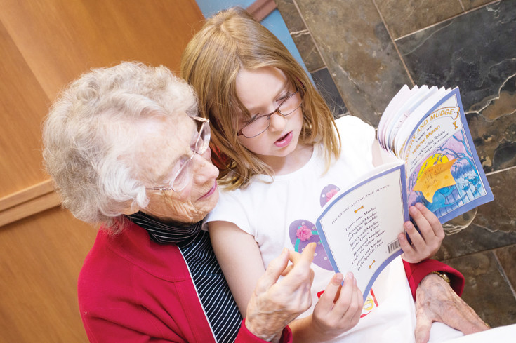 Alice Hulings reads with her pen pal, Katie Boyes on April 28 at the Holly Creek Retirement Community.