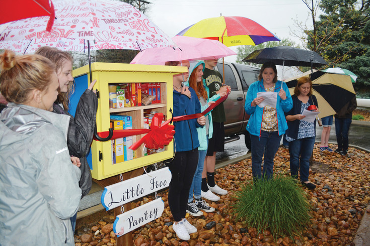 Heritage High School students and parents gather in the rain to dedicate a Little Fee Pantry in Littleton on May 8.