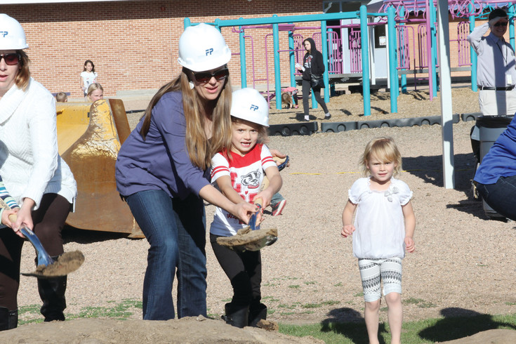 Vanessa Fritzsche gets help from kindergartner Maddy Walcott in tossing dirt that was part of the May 11 ceremonial groundbreaking for construction of the new Charles Hay World School. Students, parents and district officials took part in the event in preparation for launching phase one of Englewood School District project that will construct four new elementary schools and a new early childhood education center.