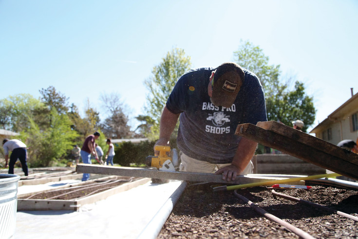 Brian Sassolino, of Lakewood, cuts wood on a volunteer workday at the Foster Elementary Community Garden in Arvada.