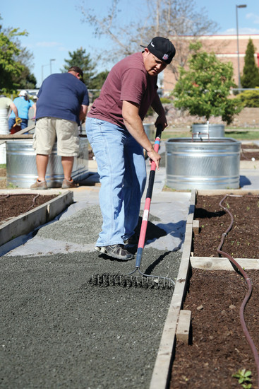 Community volunteer Jackie Rodriguez helps smooth out the foundation for the garden at Foster Elementary School.
