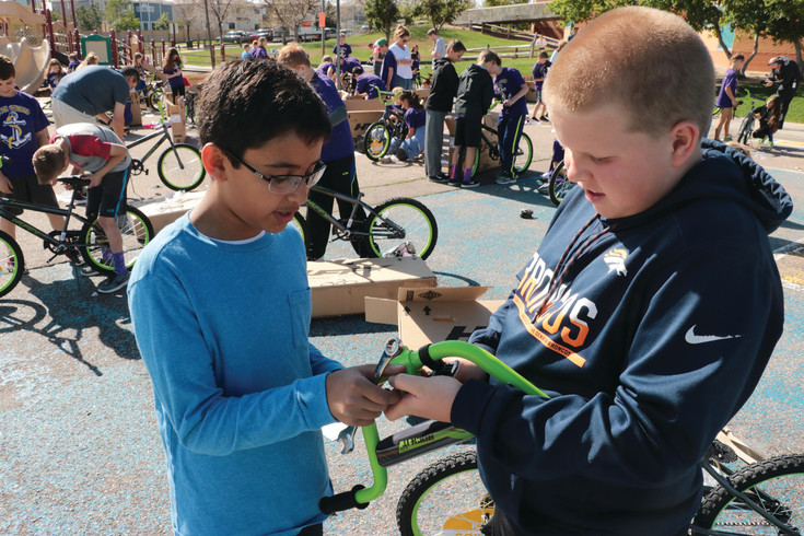 Fifth-graders Shuban Dhawan, left, and Sam Schiel demonstrate teamwork as they try to assemble a handlebar for a bicycle on May 9 at Summit View Elementary School, 10200 Piedmont Drive.