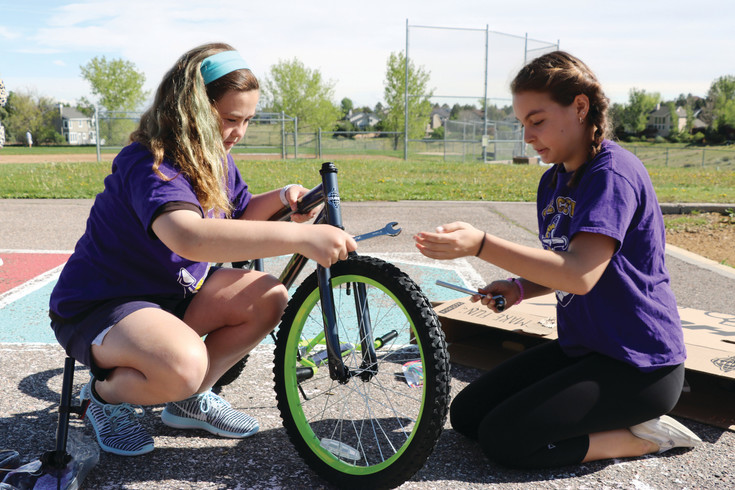 Karter Schwartzkopf, left, and Nina Pollack, fifth-graders at Summit View Elementary School, assemble a bike that will go to a kindergartner at Sedalia Elementary School.