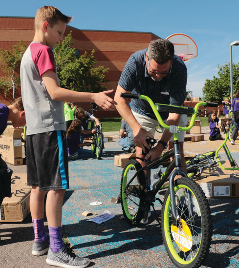 "Davin Hendee, left, and Matt Witt assemble a bike the morning of May 9 at Summit View Elementary School. Witt, with Silver Leaf Mortgage, was one of the sponsors of the event. ""Every kid wants to have a bike,"" he said. ""Kids ride bikes like crazy — I did as a kid."""