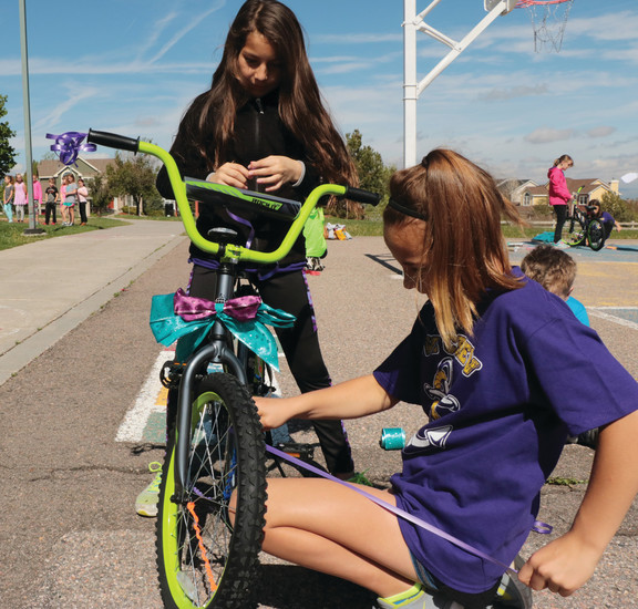 Aviana Arroyo, left, and Avelyn Latka put the final touches on a bike that will be given to a  kindergartner of Sedalia Elementary School.