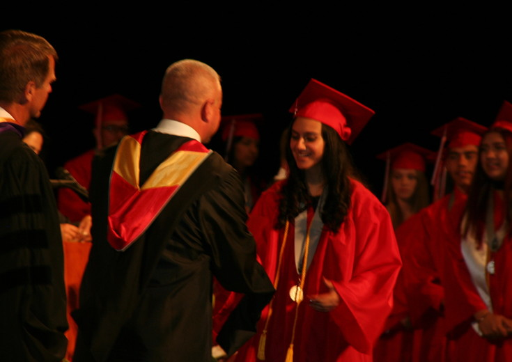 Jennifer Alexa Flores shakes Jefferson High School Principal Michael James' hand as she walks up to accept her diploma at the school's 2017 graduation ceremony on May 17 at Ellie Caulkins Opera House in downtown Denver.