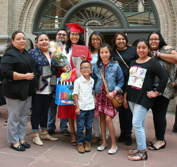 Yulissa Valles Ramirez and her family gather outside of the Ellie Caulkins Opera House in downtown Denver after the 2017 Jefferson High School graduation ceremony on May 17.