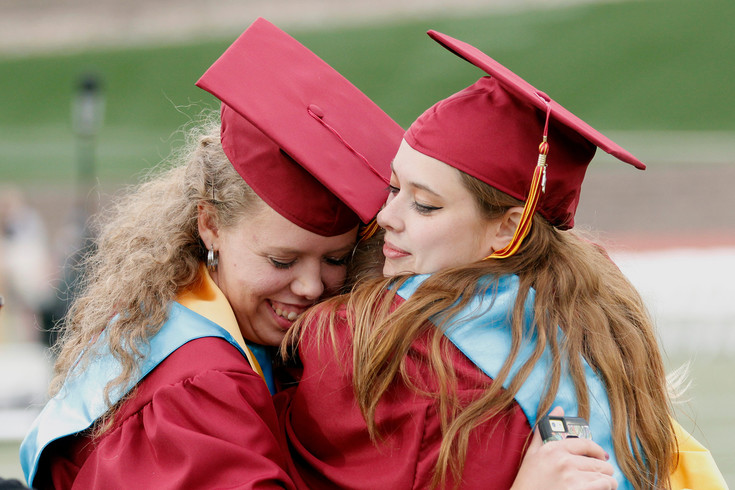 "Ponderosa High School graduatesMichaela Udlock, left, and Laruen Dickinson, right, embrace each other and 2016 Ponderosa graduate Liz Schmidt, sandwiched between them. Schmidt says Udlock and Dickinson are her best friends and came to the ceremony because she's ""just so proud of them."""