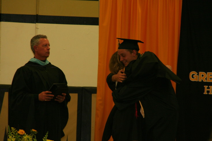 Joshua William Phillips hugs Green Mountain High School Principal Colleen Owens as he receives his diploma at the school's commencement ceremony on May 18.
