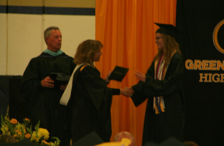 Principal Colleen Owens, left, shakes Sara Rebecca Clark's hand as she hands the 2017 graduate her diploma at the Green Mountain High School commencement ceremony on May 18.