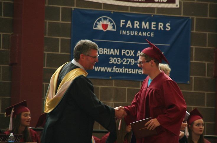 Tyler James Griffin, right, smiles as he shakes Golden High School Principal Brian Conroy's hand at the school's 2017 commencement ceremony on May 19.