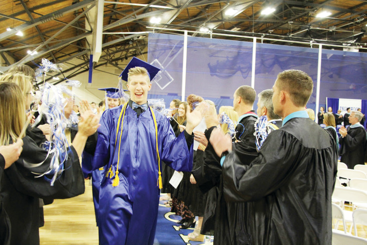 Sam Westra slaps hands with faculty members as he and the other members of the Englewood High School Class of 2017 march to their seats at the start of the May 20 commencement ceremonies held in the Englewood High School Field House. Diplomas were presented as 112 EHS students became EHS alumni.