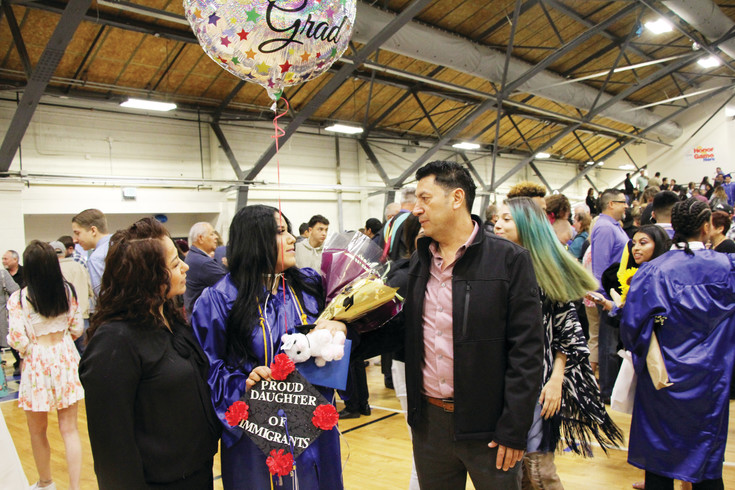 "Rosa Ramirez, holds her hat declaring she is, ""A proud daughter of immigrants"" as she talks with her dad Jose Ramirez, right, and her mother Petra Banuelos following the May 20 Englewood High School Commencement Ceremony that was held in the EHS Field House. Diplomas were presented to the 112 members of the Class of 2017 during the ceremony."