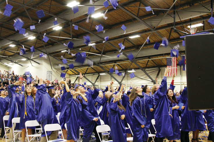 Hats fly into the air May 20 as 112 Englewood High School students celebrate becoming alumni. The hat toss concluded the 104 EHS commencement ceremony that, because of weather, was held in the Englewood High School Filed House.