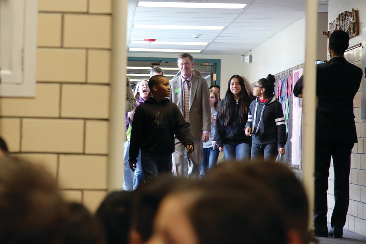 Foster Elementary School students lead Governor John Hickenlooper down the halls of their school.