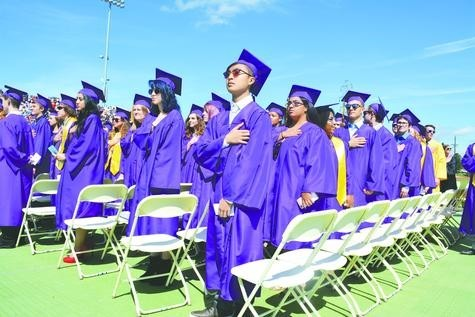 Littleton High School's newest graduates stand for the national anthem before graduation on May 26.